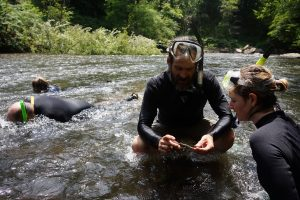 Photo: Steve Fraley show Erin McCombs a crayfish. Credit: G. Peeples